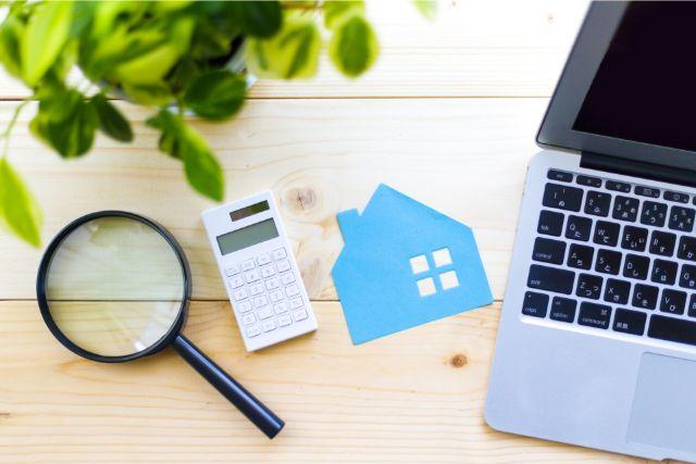 地価を調べるためのノートパソコンと電卓