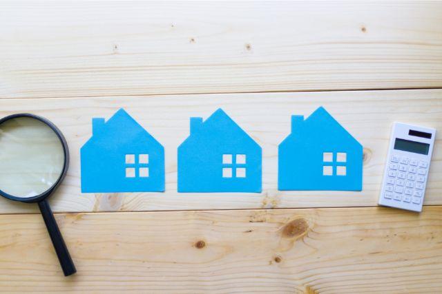 電卓と虫眼鏡の間に並んだ色紙の家
